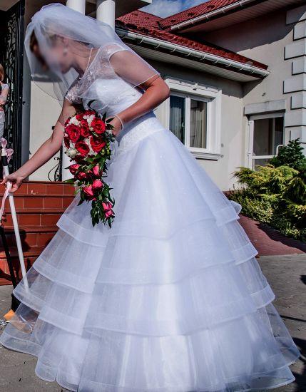 Cena : 1000 PLN. Rozmiar : 36-38. Suknia ślubna  Koronka I Princeska Firmy . Opis :Gorset zdobiony koronką,pod którą są cekiny.Dół sukni z falban z połyskującego materiału. Suknia na elastycznych krynolinach.Rozmiar na wzrost od 155 do 170cm.Moje wymiary:biodra 92cm,pas 78cm,biust(miseczka B/C) 84 cm.