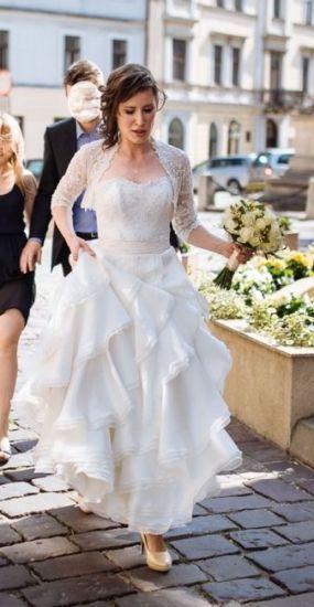 Cena : 1000 PLN. Rozmiar : 36,38. Suknia ślubna  Ambrosia Firmy Fulara & Żywczyk. Opis :Cudowna suknia, która przynosi szczęście! Zwiewna, z lejącymi się kaskadowo falbanami oraz oryginalną koronką hiszpańską. Pas został wykonany z pięknego perłowego szantungu. Całość jest niezwykle wygodna i pozwala na zabawę do białego rana. W kompelcie znajduje się koronkowe bolerko oraz krawat z szantungu w stylu angielskim. Suknia nie posiada śladów użytkowania. GRATIS nieużywane, skórzane czółenka!