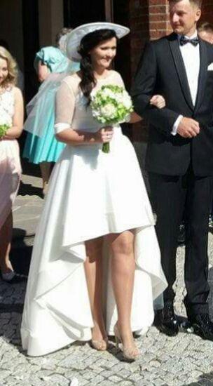 Cena : 1500 PLN. Rozmiar : 38,40. Suknia ślubna  Dorika Firmy Madonna. Opis :Asymetryczna suknia ślubna w kolorze ivory (śmietanowym). Wymiary:na wzrost 168 cm + obcas 10-12 cm), zapinana z tyłu na suwak. Suknia jest lekka, wygodna. Jest po czyszczeniu chemicznym. W zestawie: -bolerko z rękawkiem 3/4, -KAPELUSZ!