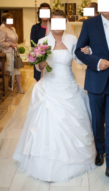Cena : 800 PLN. Rozmiar : 36,38. Suknia ślubna   Firmy . Opis :Biała sukienka z tafty z efektownym drapowaniem gorsetu (wyszczupla). Na dole posiada odsłoniętą halkę z kreszowanej organzy. Dodatkowo zdobią sukienkę połyskujące hafty. W zestawie jest białe bolerko, długi welon i halka. Jest bardzo wygodna i nie krępuje ruchów.