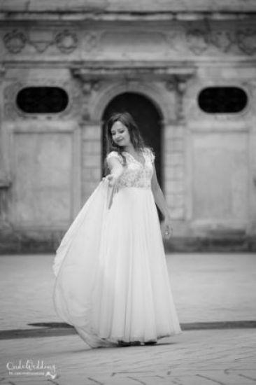 Cena : 1500 PLN. Rozmiar : 34. Suknia ślubna  Rina Firmy Kaledonia. Opis :Kolor ecru, w górnej części na koronce znajdują się przeźroczyste cekiny. Szyta na wzrost ok. 160 cm + 5-7 cm obcas, rozmiar 34/36. Zapinana na zamek i guziczki, tren podpinany.