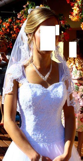 Cena : 700 PLN. Rozmiar : 36,38. Suknia ślubna   Firmy . Opis :Suknia ślubna princeska z haftowanym welonem hiszpańskim. Haftowane ramiączka, gorset oraz dół sukni wraz z welonem tworzą piękny zestaw. Bardzo wygodna i pięknie podkreśla talię.