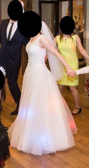 Cena : 800 PLN. Rozmiar : 36,38. Suknia ślubna   Firmy Evita. Opis :Suknia z salonu Evita w kształcie litery A z koronkową górą i plecami, ze srebrnym paskiem. Wygodna, pięknie układa się w tańcu.
