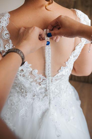 Cena : 1300 PLN. Rozmiar : 38,40. Suknia ślubna  Estera Firmy Skalimar. Opis :Suknia kupiona w salonie dom mody w Nysie. Do sukni wszyte kryształy - transparentne. Odbijają światło w różnych kolorach. Suknia ma tren podpinany na jednym guziku. Pięknie zdobione plecy - półprzeźroczyste z motywem koronki kwiatowej. Do sukni wszyty biustonosz.