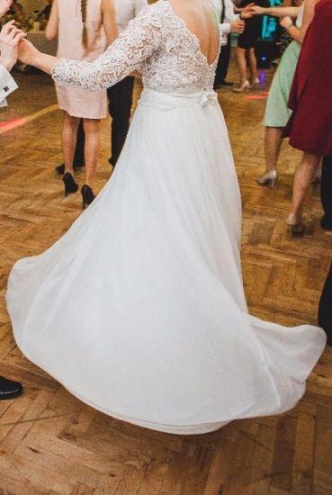 Cena : 890 PLN. Rozmiar : . Suknia ślubna   Firmy . Opis :Suknia szyta na wzrost 167 cm plus 10 cm obcasy. Rozmiar 40. Góra sukni koronkowa, nie usztywniana, z wszytymi miseczkami biustonosza. Dół sukni muślinowy + tren dopinany na trzy niewidoczne guziczki (bardzo wygodne, w każdej chwili można odpiąć).